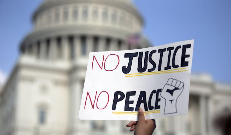 """Des manifestants, par milliers, ont lancé le slogan """"No Justice, No Peace"""" devant la maison blanche"""